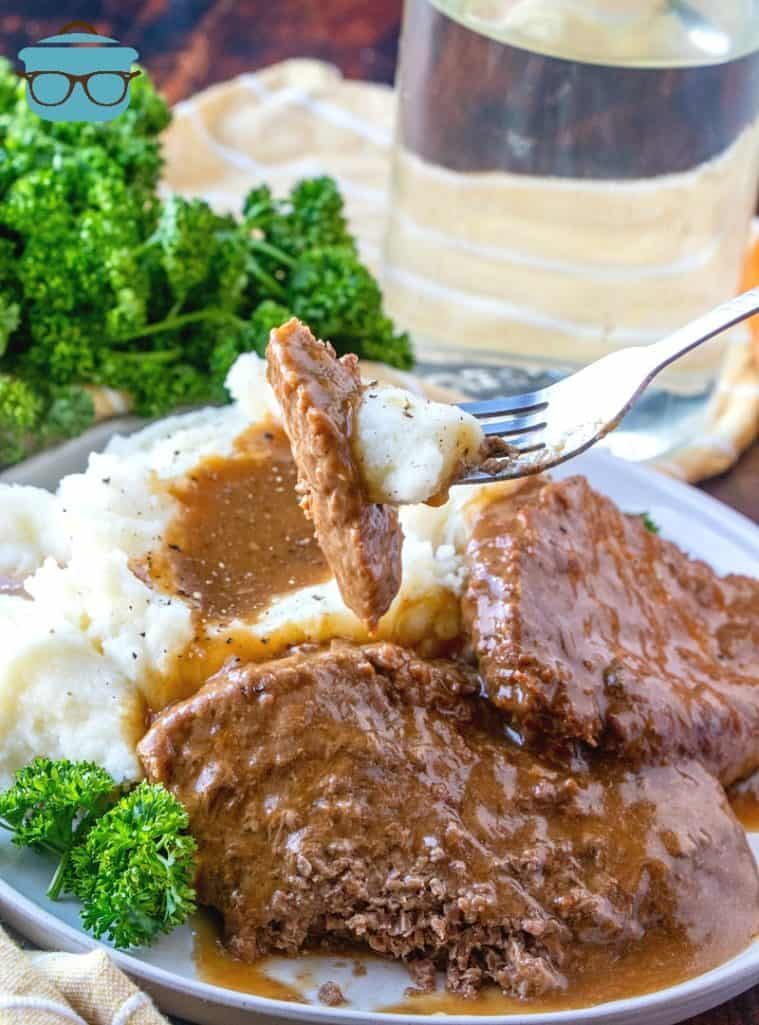 Instant Pot Cubed Steak with Gravy served on a white plate with mashed potatoes and parsley in the background