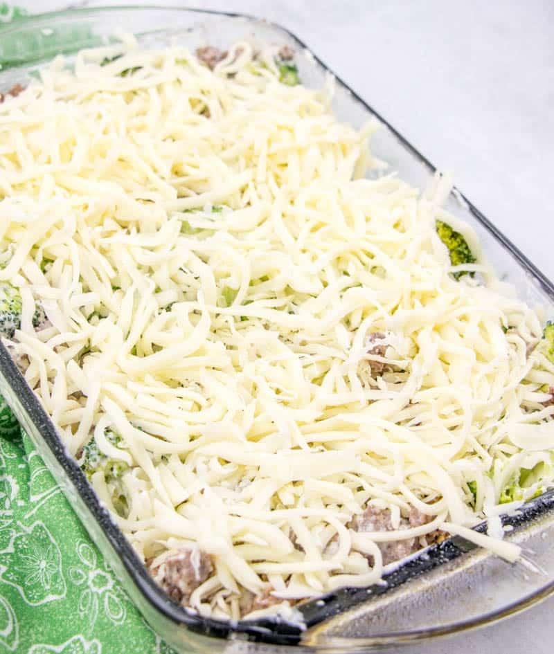 shredded mozzarella cheese on top of ground beef, sausage, cream sauce