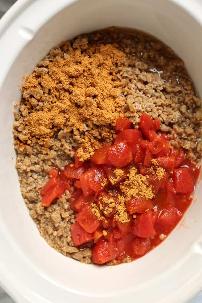 cooked ground beef, diced tomatoes, taco seasoning and water in crock pot