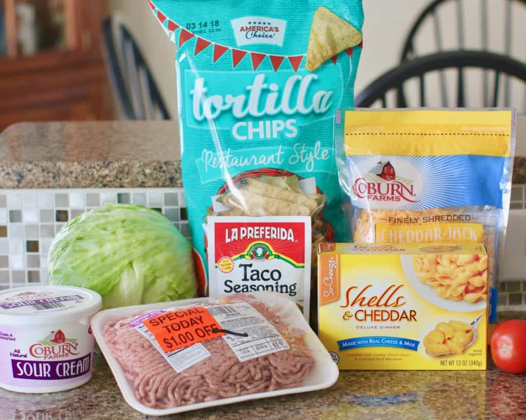 ground beef, packet taco seasoning, boxed macaroni and cheese, lettuce, tomato, sour cream, tortilla chips, shredded cheddar jack cheese,
