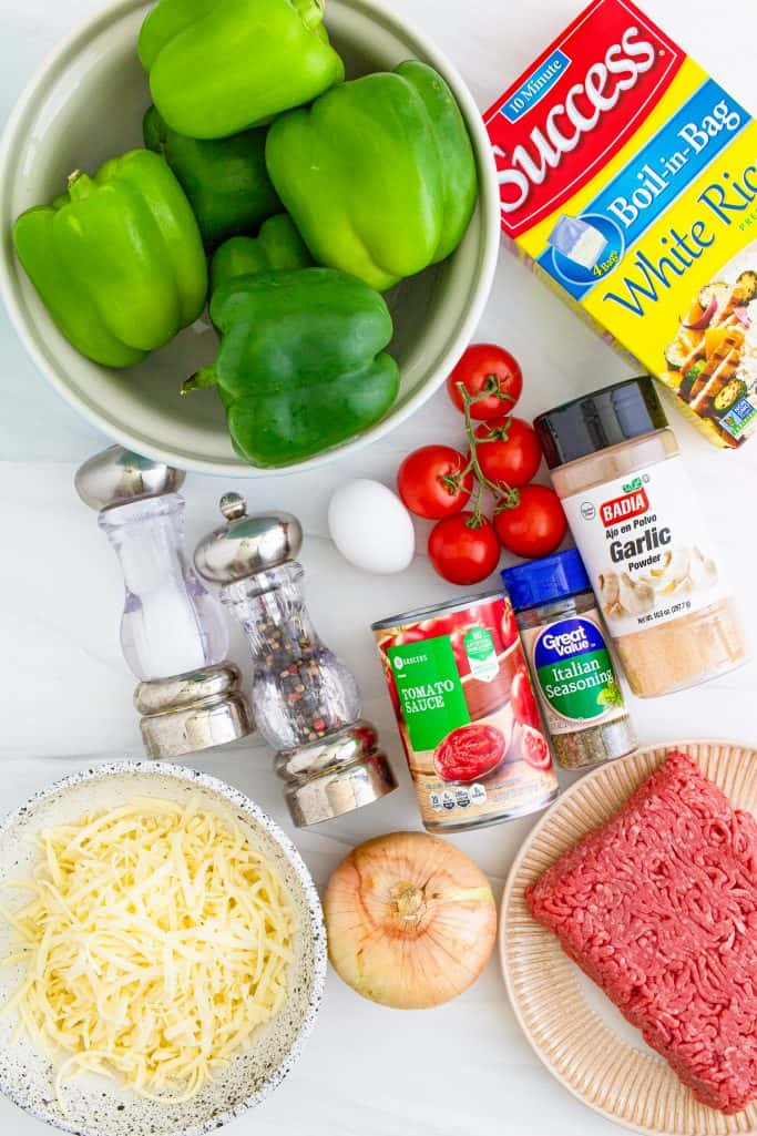 Instant Pot Stuffed Peppers ingredients: green bell peppers, onion, tomatoes, extra lean ground beef, boil-in-bag white rice, large egg, salt and pepper, Italian seasoning, garlic powder, tomato sauce, shredded mozzarella cheese