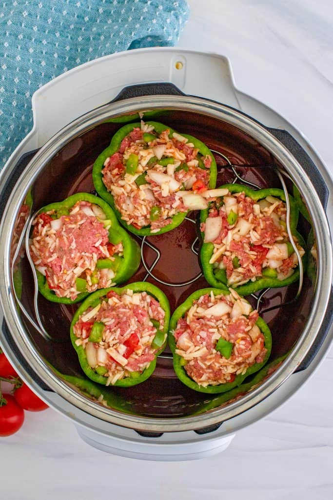 trivet holding 5 stuffed peppers placed inside the instant pot