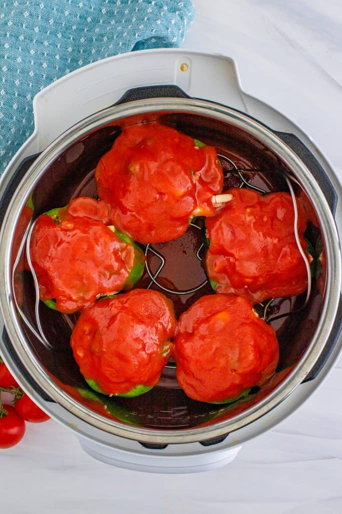 tomato sauce evenly spread on top of stuffed peppers