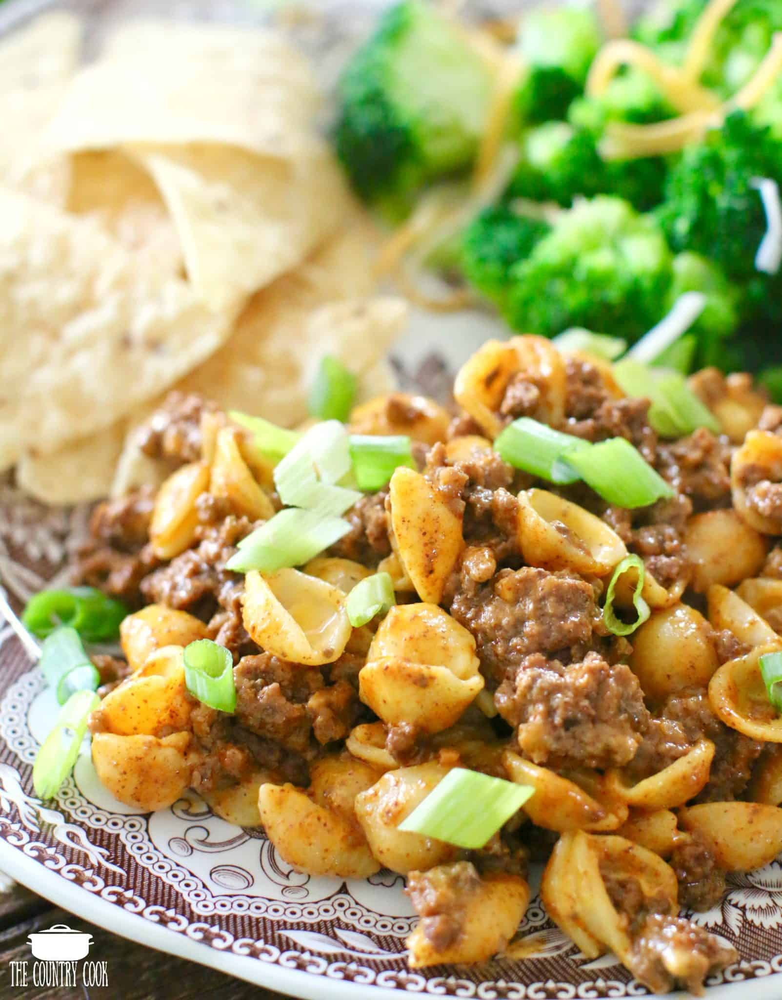 Easy Taco Macaroni and Cheese serving on a plate and topped with sliced green onions.