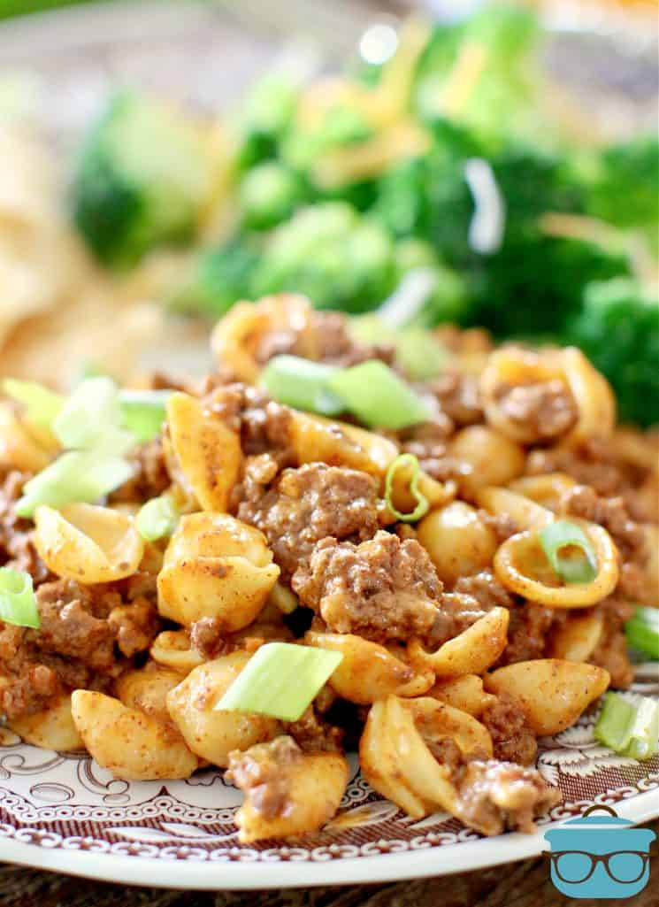 Easy Taco Macaroni and Cheese, serving shown on a plate, with a string of steamed broccoli
