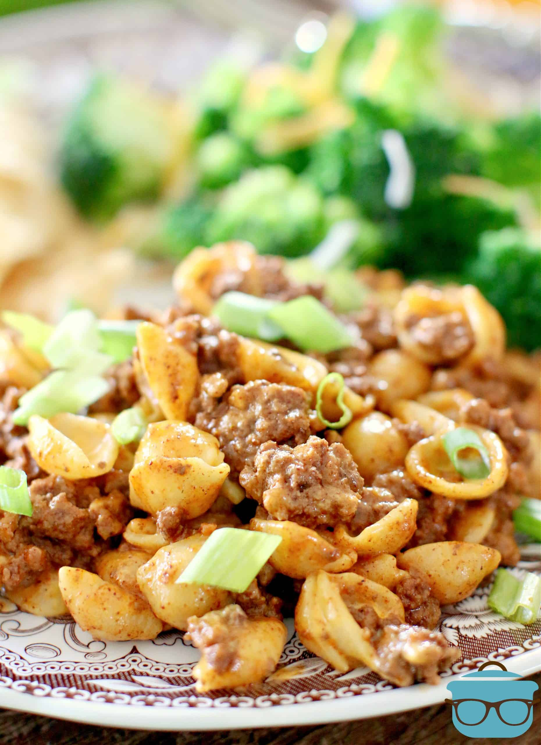 Easy Taco Macaroni and Cheese, serving shown on a plate, with a string of steamed broccoli.