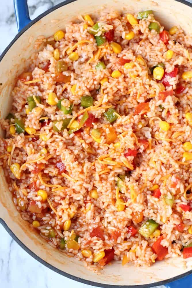 cooked rice, peppers, enchilada sauce, frozen corn, Rotel diced tomatoes and shredded cheese stirred together in a large oven-safe Le Creuset skillet