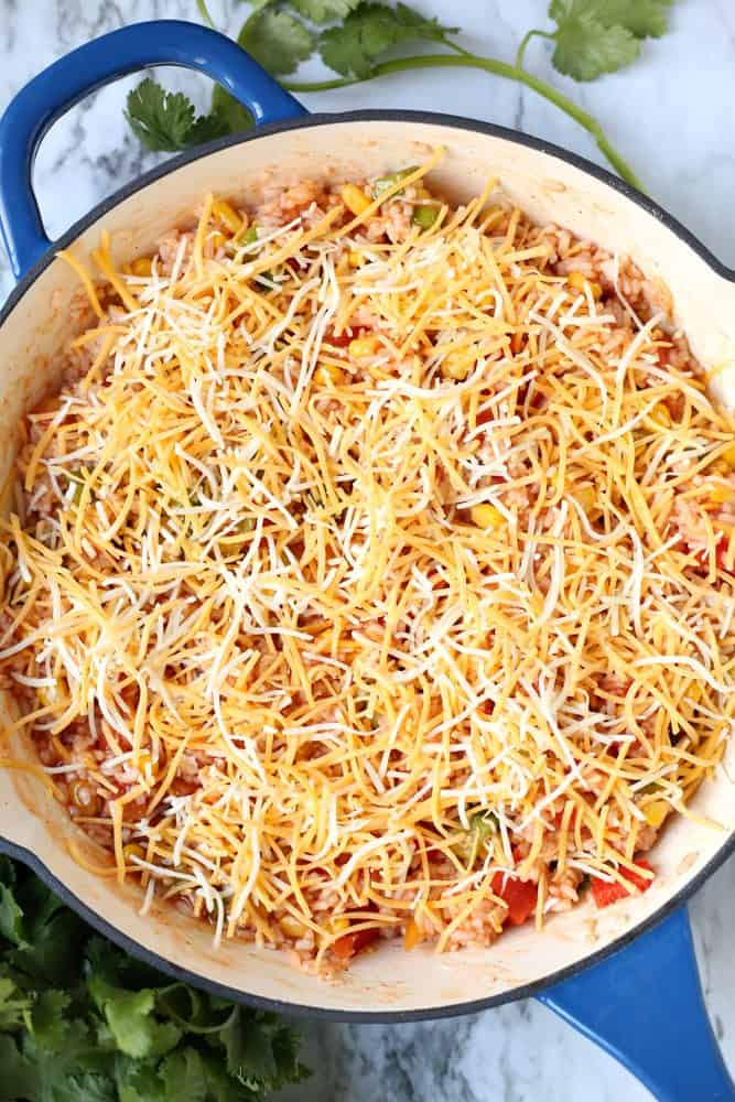cooked rice, peppers, enchilada sauce, frozen corn, Rotel diced tomatoes and shredded cheese stirred together in a large oven-safe Le Creuset skillet covered with shredded cheese