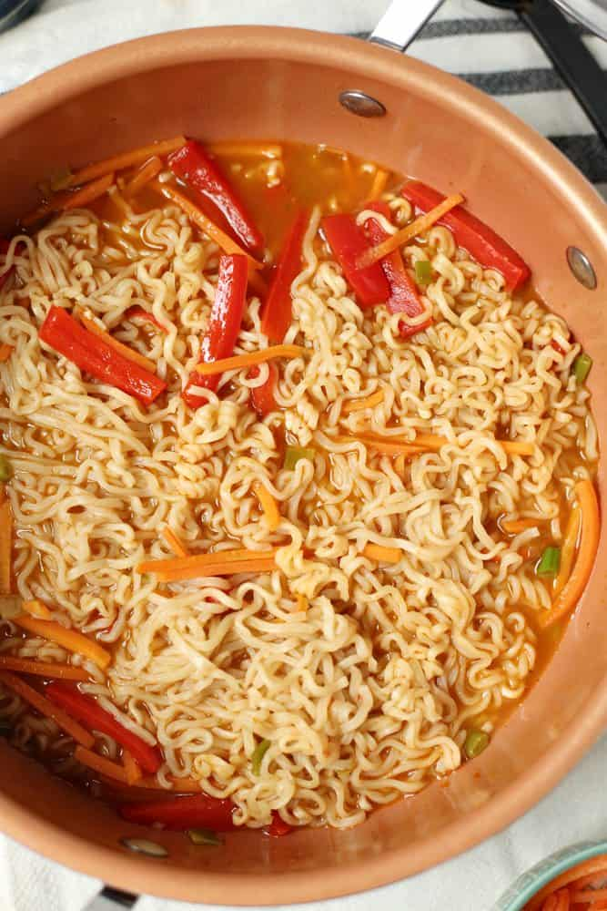 cooked vegetables added into pot with vegetable broth and ramen noodles