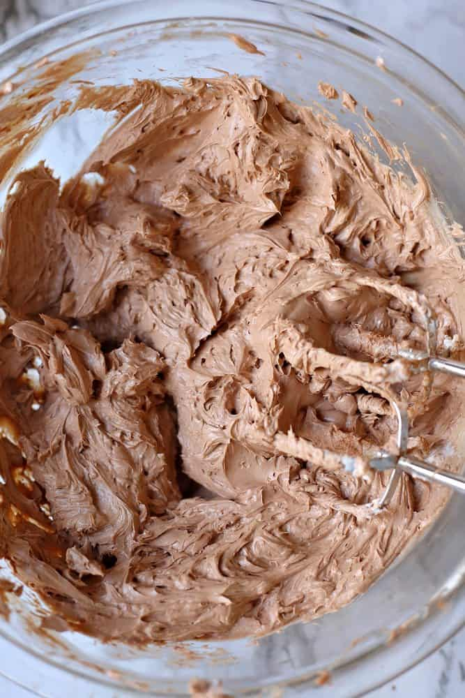 cream cheese, butter, cocoa powder, powdered sugar, whipped cream mixed together by a handheld electric mixer