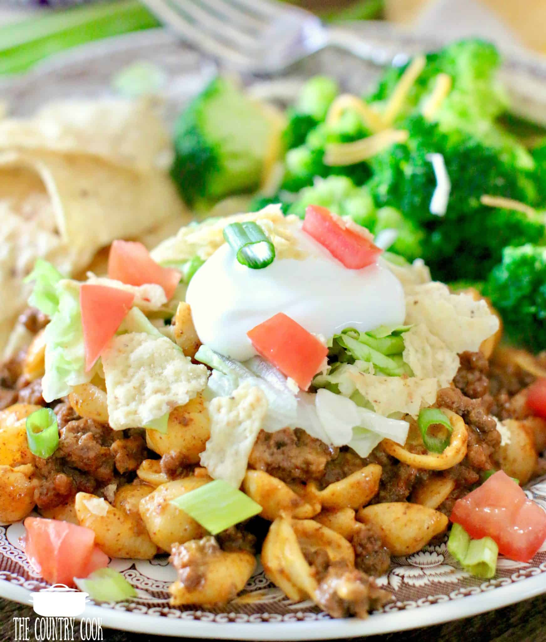 Taco Mac and Cheese topped with lettuce, tomato, tortilla chips and sour cream.