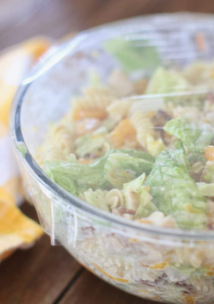 plastic wrap covered bowl with pasta, grilled chicken, lettuce, pecans and mandarin oranges