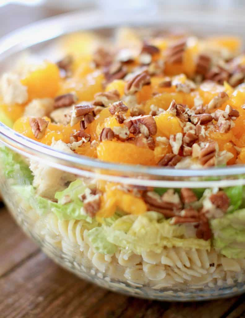 cooked rotini pasta, mandarin oranges, lettuce and chopped pecans layered in a bowl