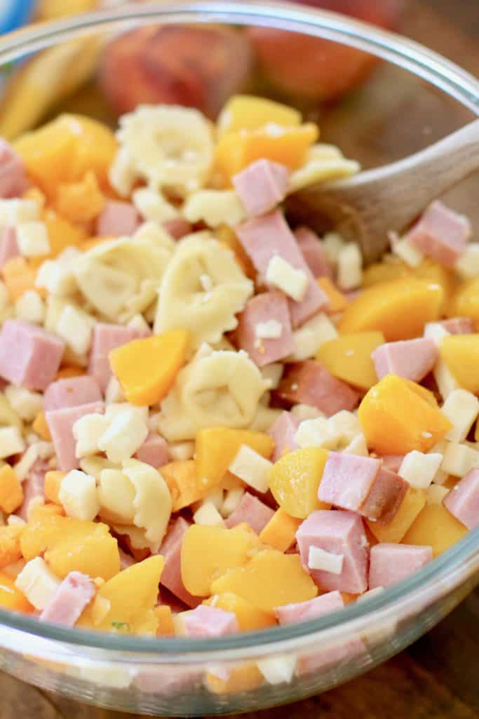 cooked cheese tortellini, diced ham, peaches, diced cheese stirred together with a wooden spoon in a large glass bowl
