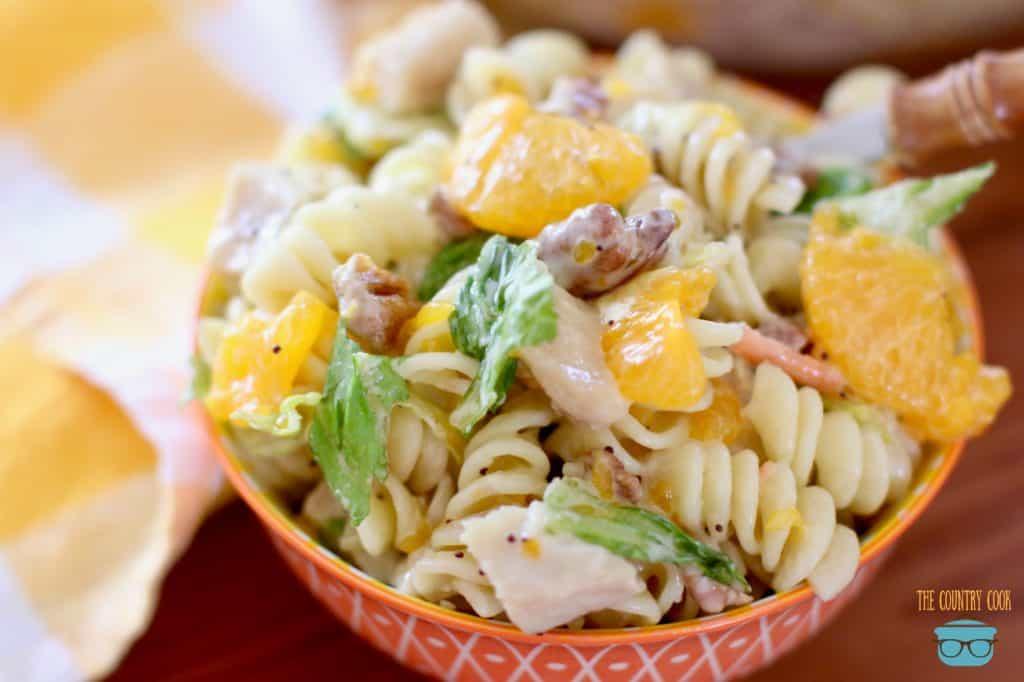 Orange Chicken Pasta Salad in an orange bowl with a fork