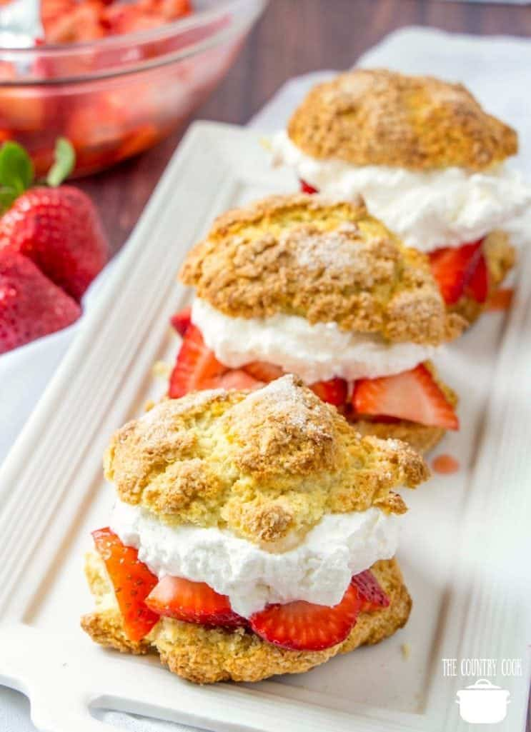 strawberry shortcakes with fresh strawberries and whipped cream on a white platter