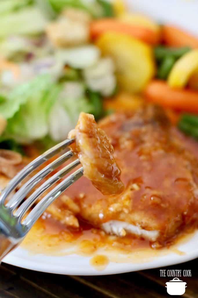 Slow Cooker Barbecue Pork Chops, sliced, on a fork