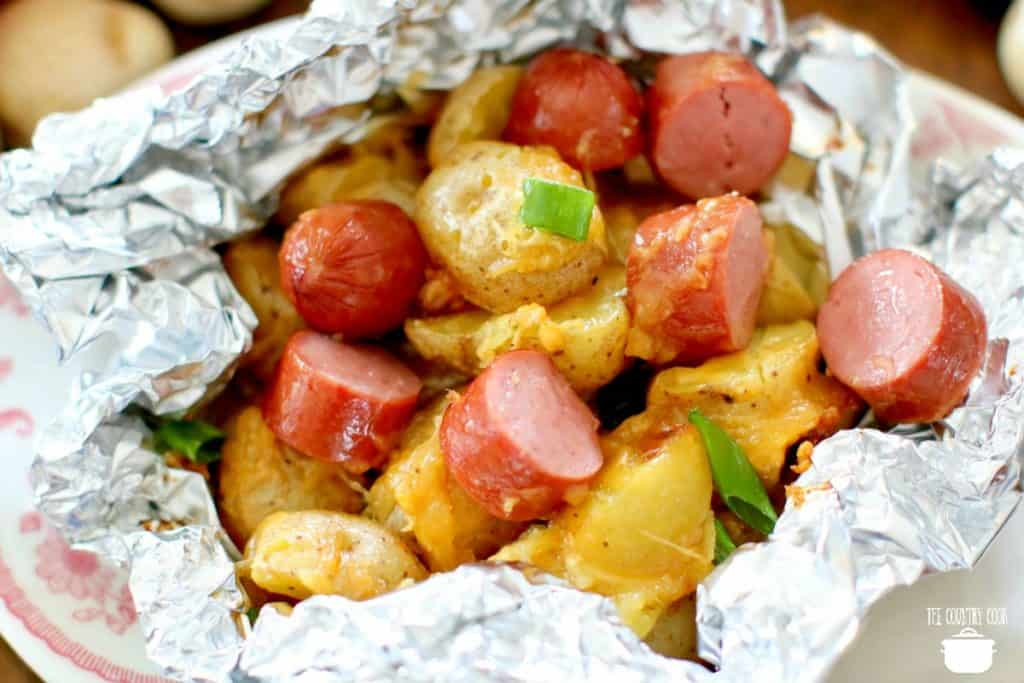 Sliced hot dogs with potato packets, cheese and green onion
