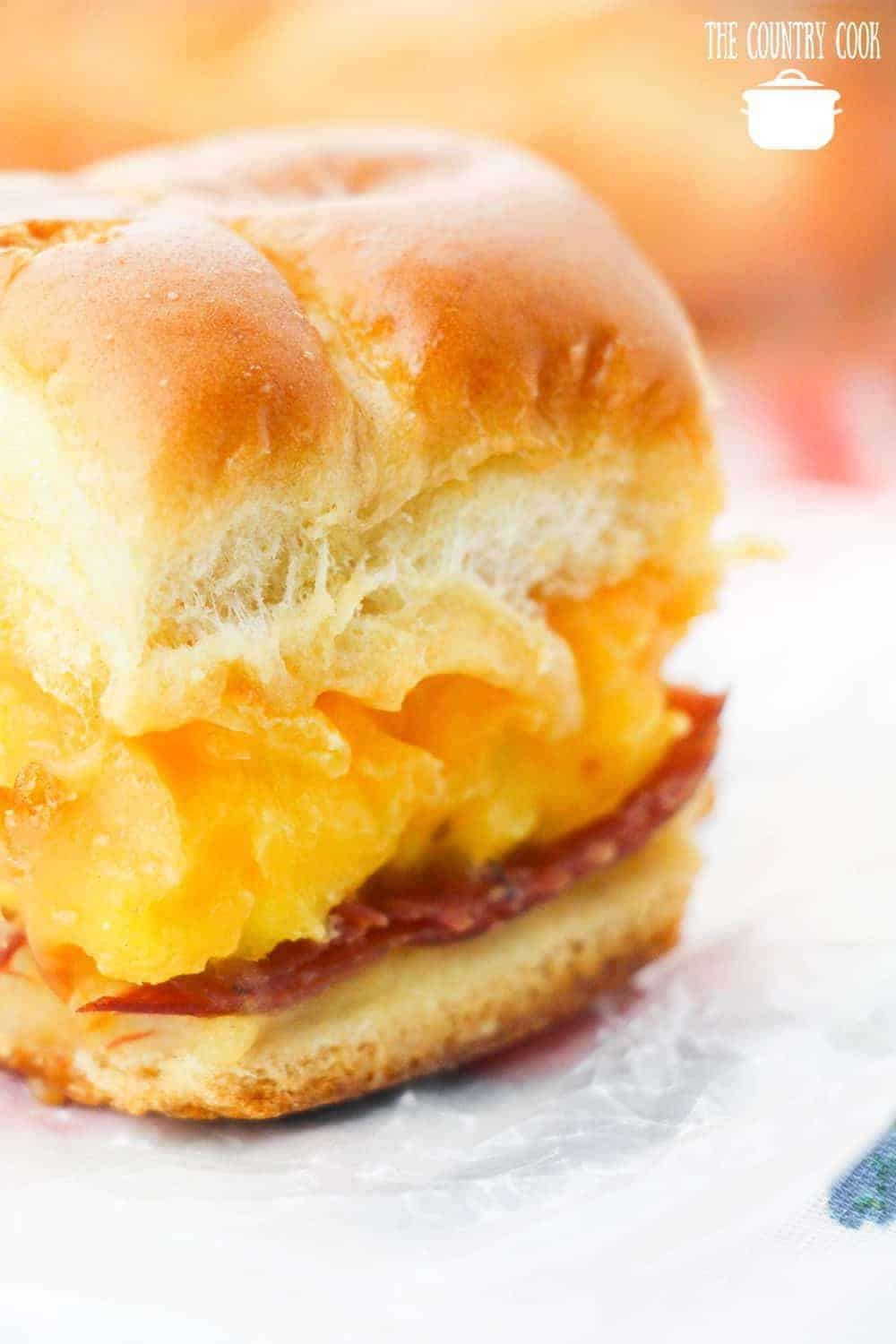 breakfast sliders with dinner rolls, scrambled eggs, cheese, ham and melted butter