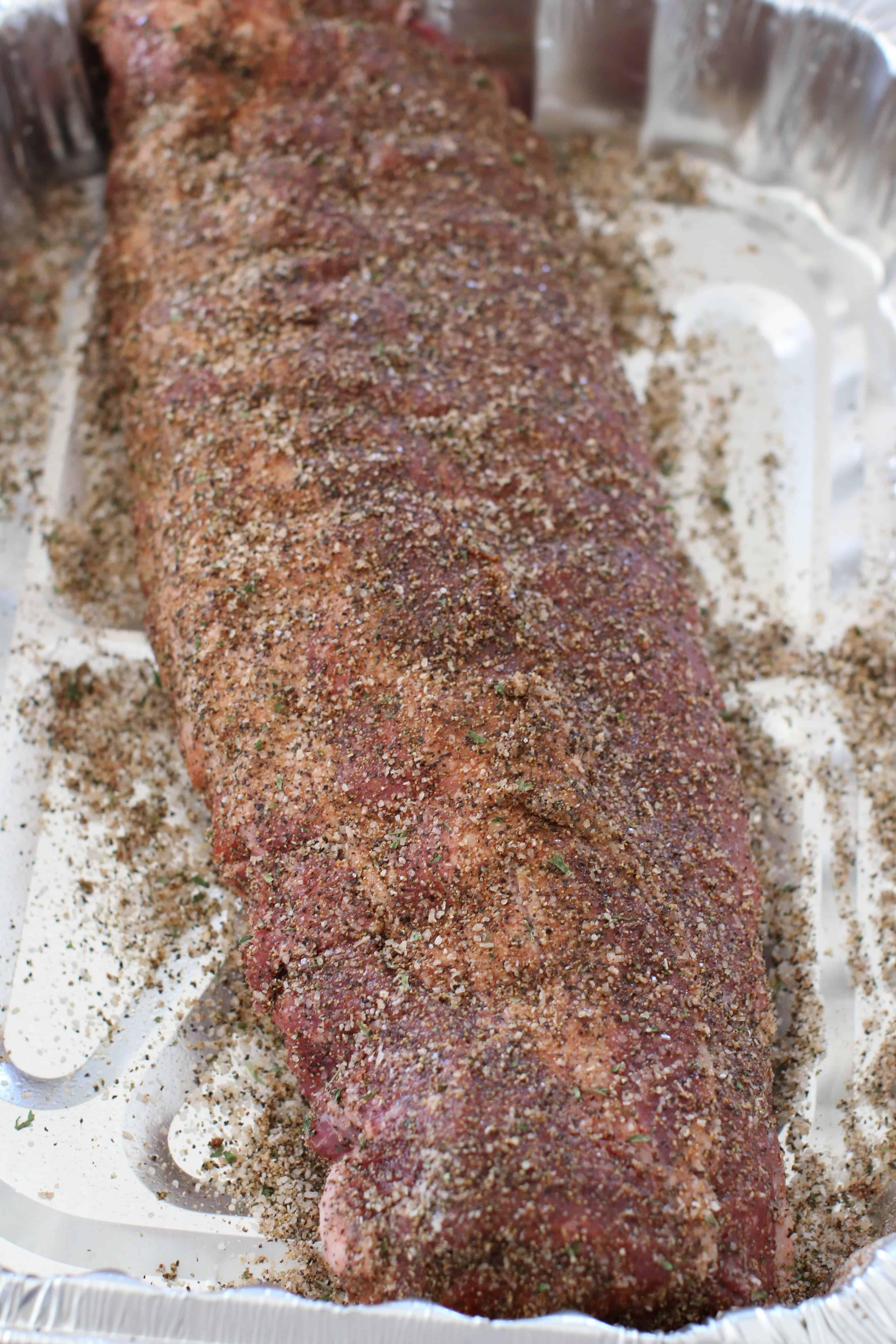 homemade pork bbq run seasoning on rack of ribs shown in an aluminum pan.