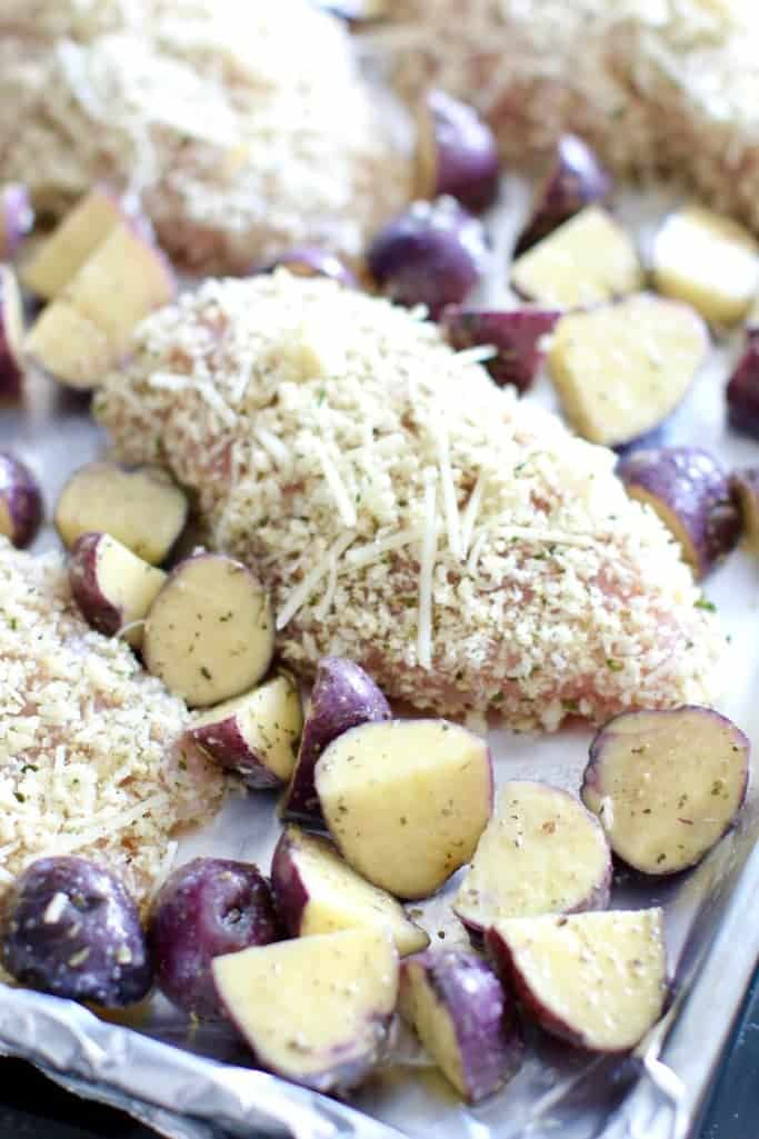 Italian seasoned diced potatoes on a baking sheet with parmesan crusted chicken