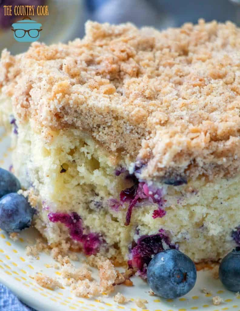 Homemade Blueberry Buckle Cake, slice on a plate with fresh blueberries