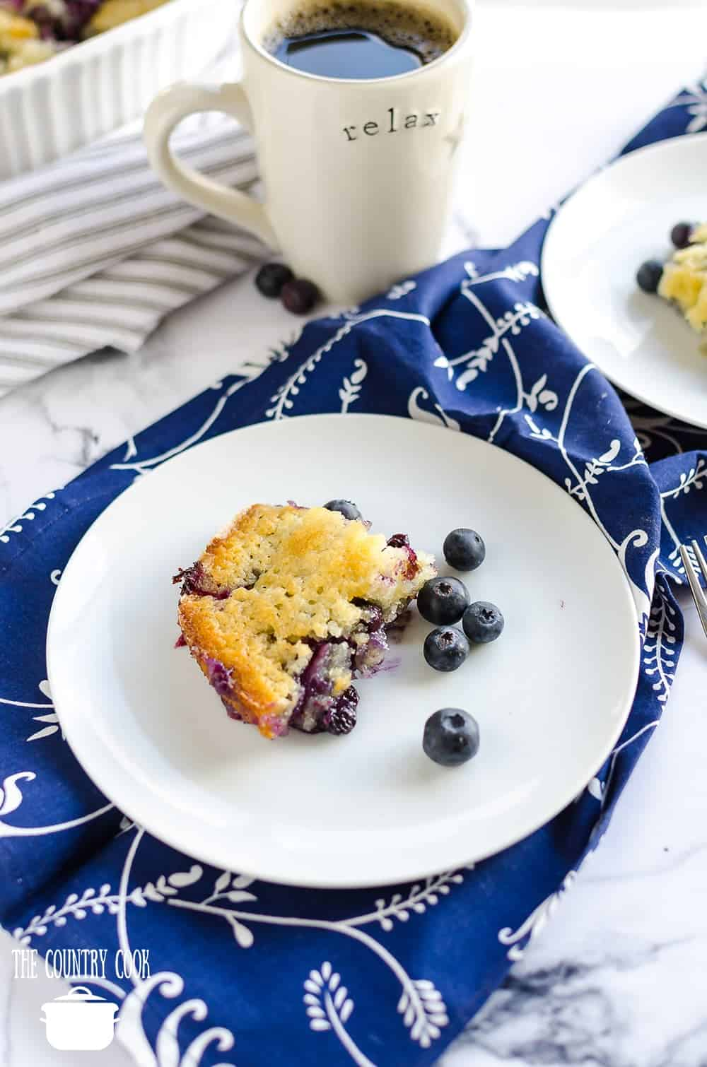 slice of fresh blueberry cobbler served with a cup of coffee