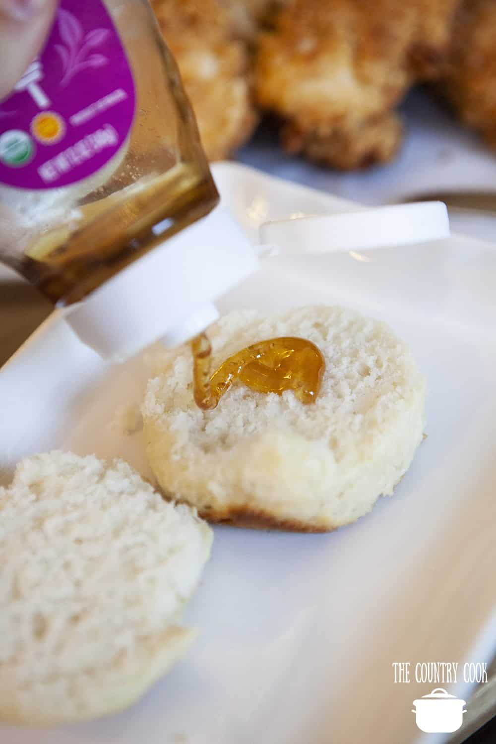 pouring honey on a homemade biscuit