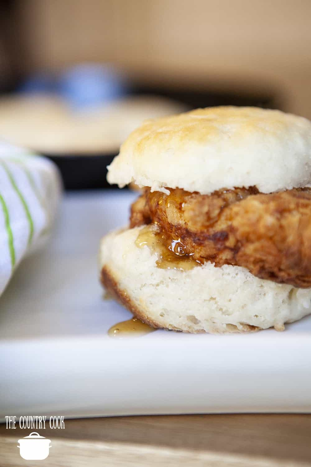 Homemade Fried Chicken Biscuit with honey on a white platter