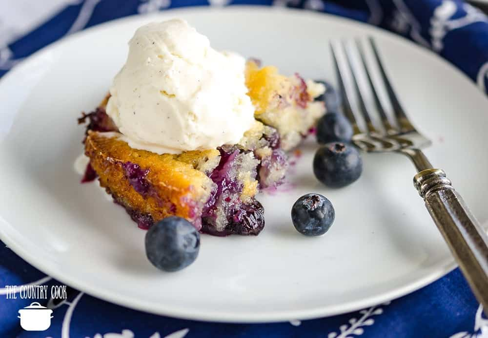 fresh blueberry cobbler topped with vanilla ice cream on a round white plate