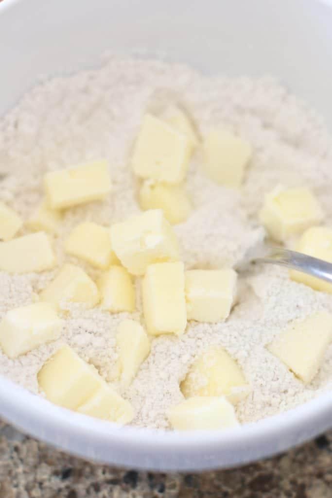 beurre en cubes salé ajouté à la farine, au sucre et au mélange de cannelle