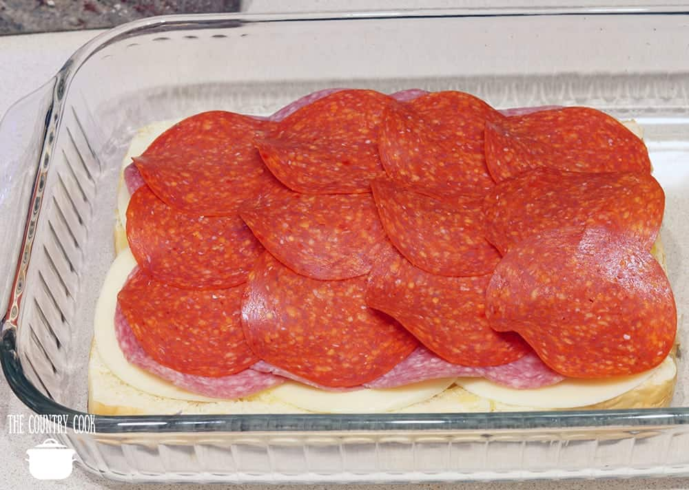 sliced Hawaiian sweet rolls topped with provolone cheese, sliced pepperoni, sliced salami in a baking dish