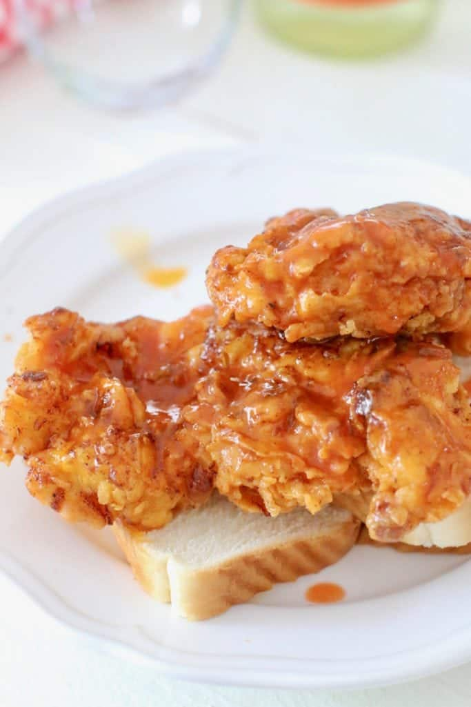Nashville Hot Chicken sauce poured on top of fried chicken breasts on white bread