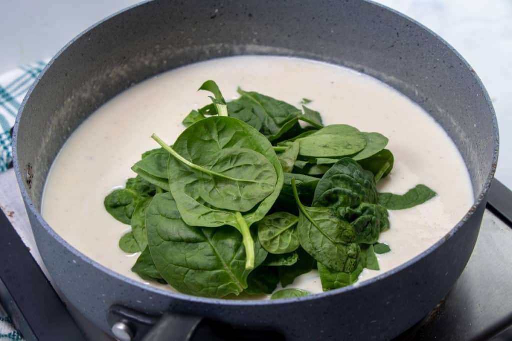 fresh spinach leaves added to thick and creamy parmesan Alfredo sauce in a large skillet