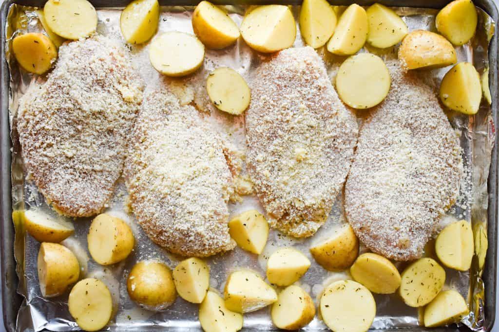 coasted chicken breasts and seasoned sliced potatoes on a large baking sheet