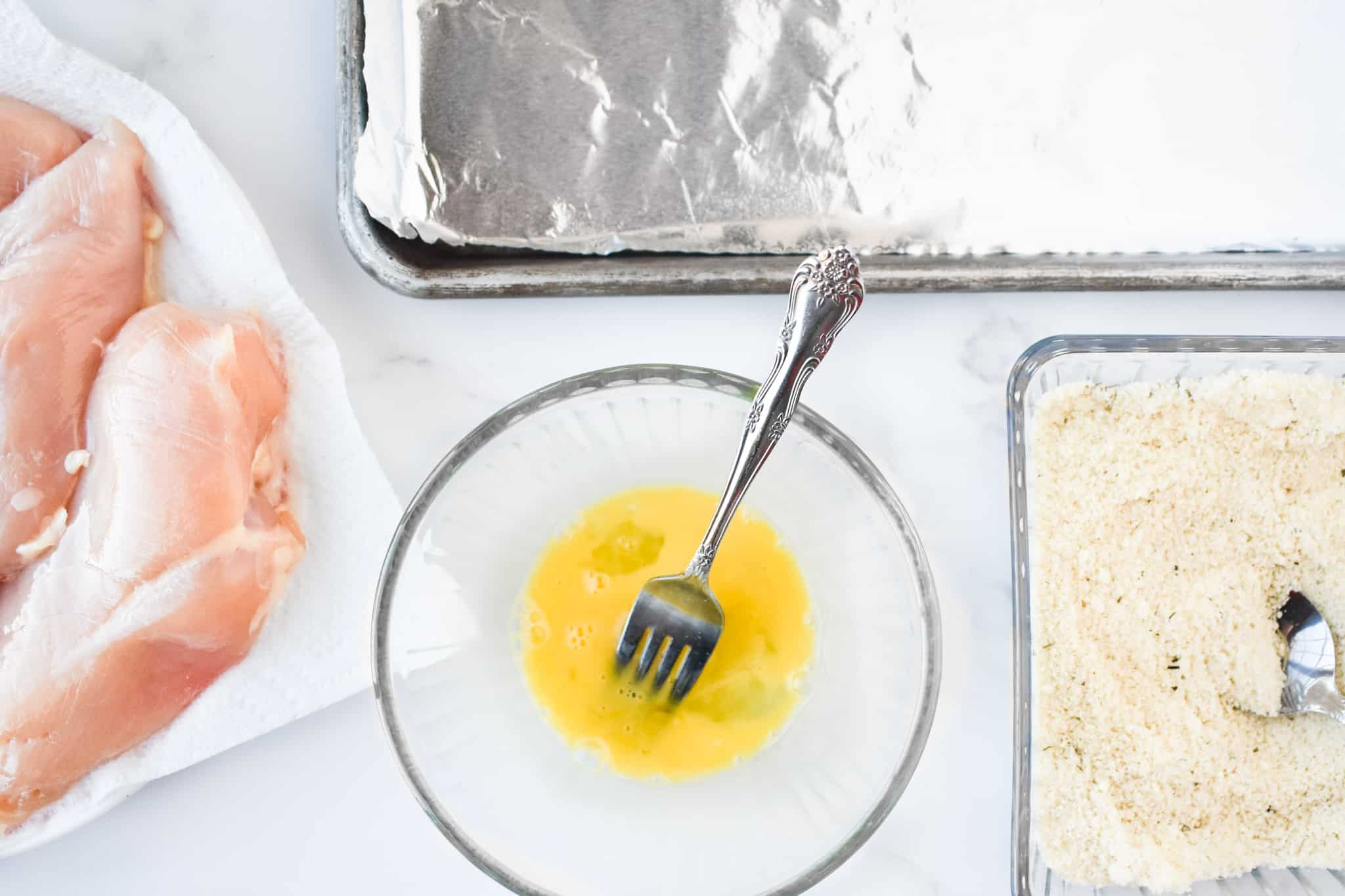 chicken breasts, sheet pan, egg yolk and panko bread crumbs in a dish.