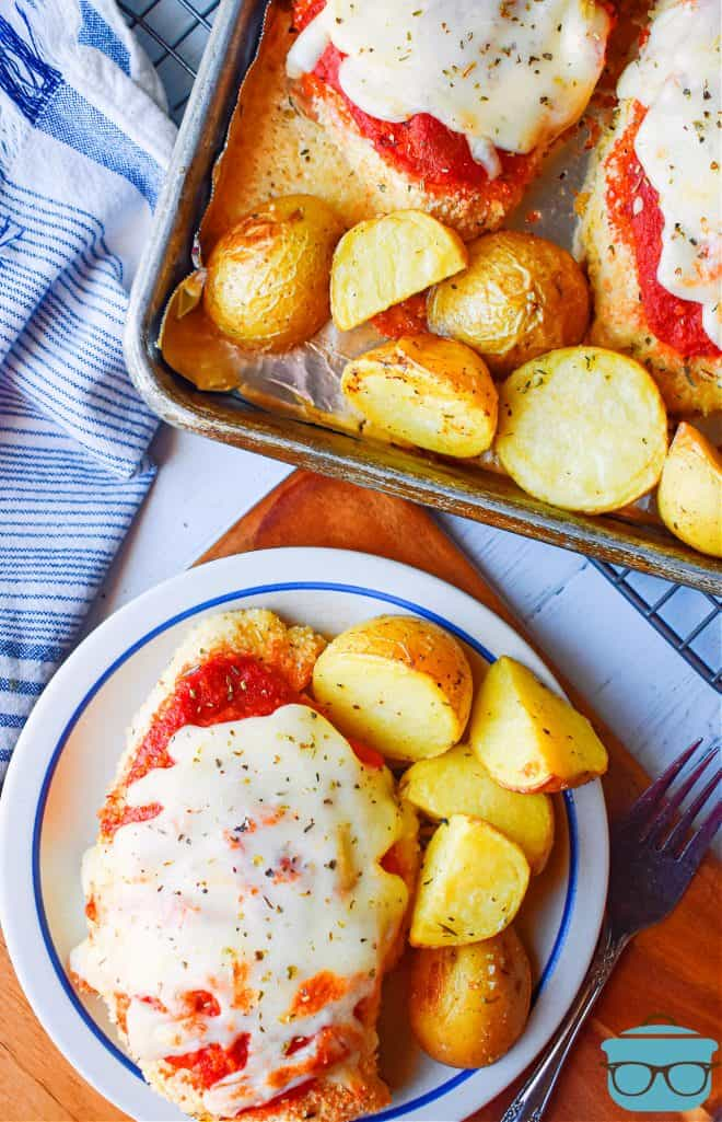 Fully baked sheet pan chicken parmesan shown on a small plate and served with roasted potatoes