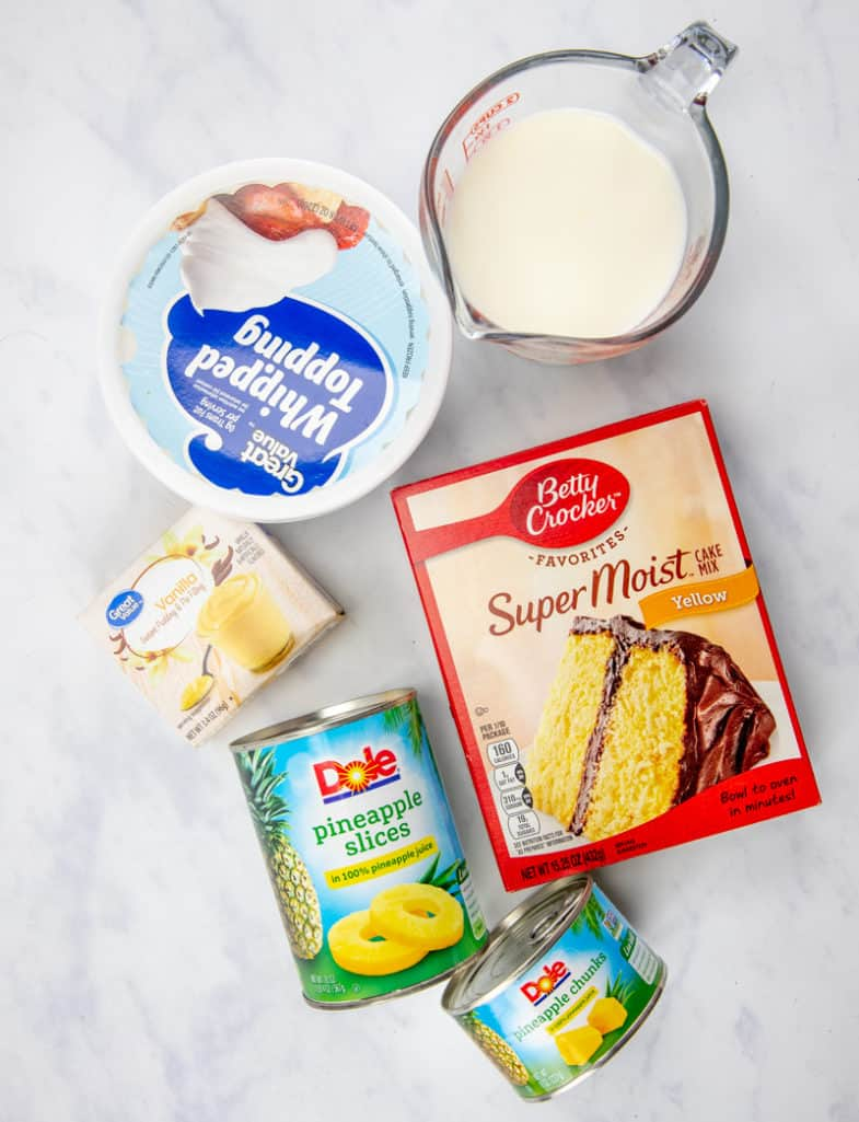 pineapple slices, yellow cake mix, eggs, oil and water, instant vanilla pudding mix, milk, whipped topping (Cool Whip), pineapple chunks