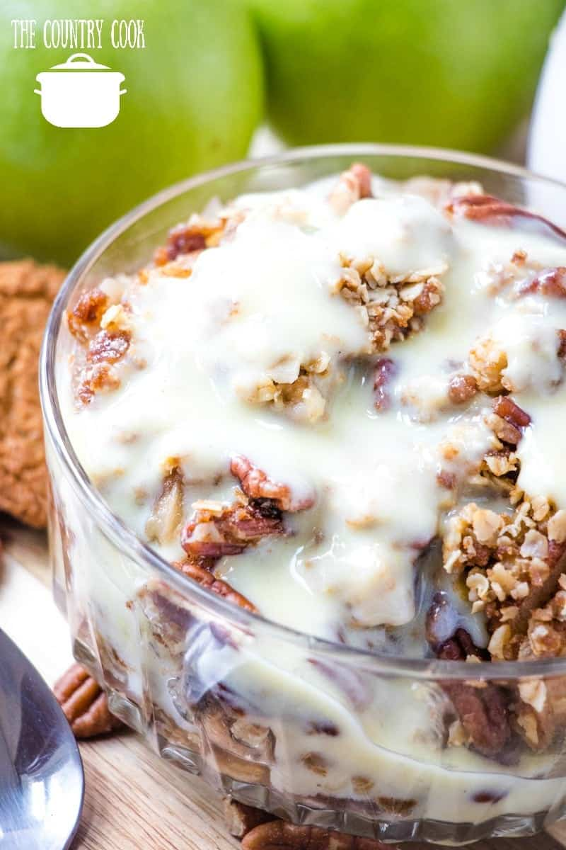 Slow Cooker Easy Apple Crisp in a bowl topped with warm vanilla sauce shown in a clear serving bowl.