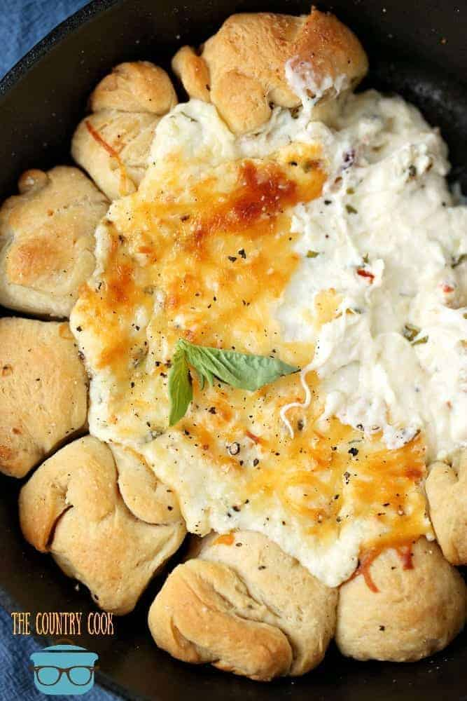 Warm Cheesy Pizza Dip baked in a cast iron skillet with refrigerated pizza dough balls for dipping