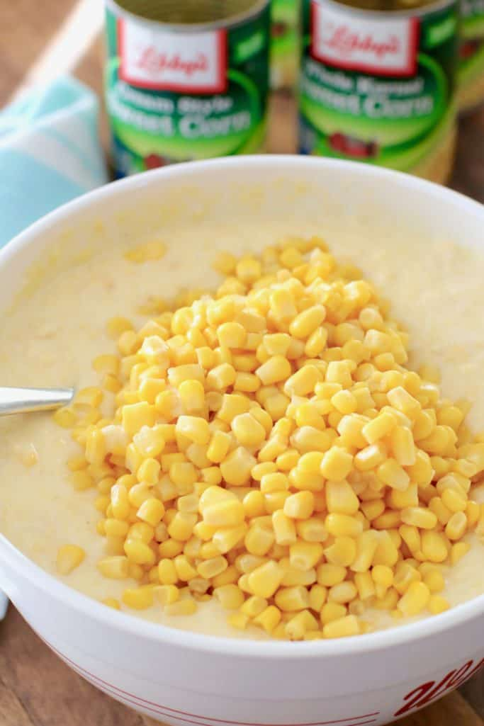 sweet corn casserole batter with canned corn down in a white mixing bowl with cans of corn in the background