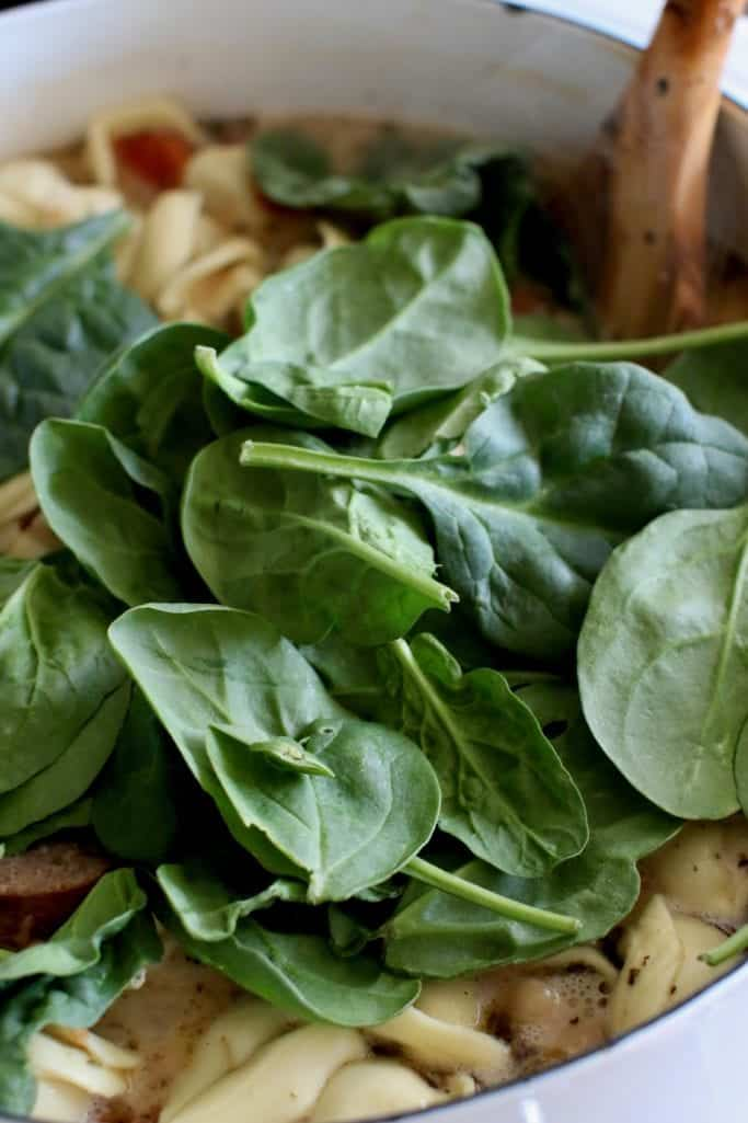 baby spinach added to Tuscan soup