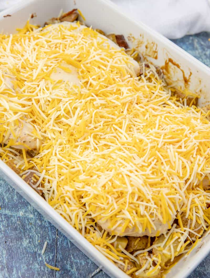 shredded cheddar cheese on chicken and potatoes in a casserole dish.