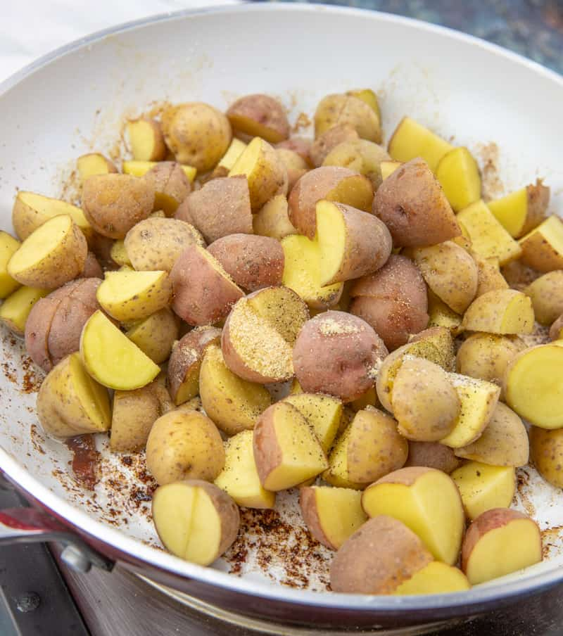 diced baby potatoes in a white skillet with seasonings added.