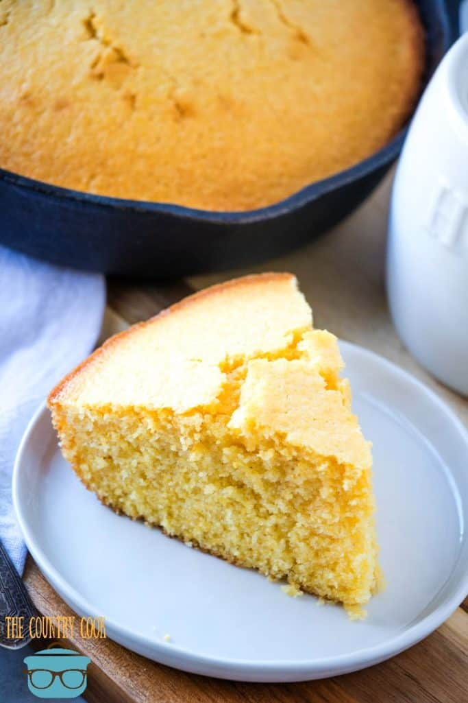 slice of cornbread on a white plate in front of cast iron skillet