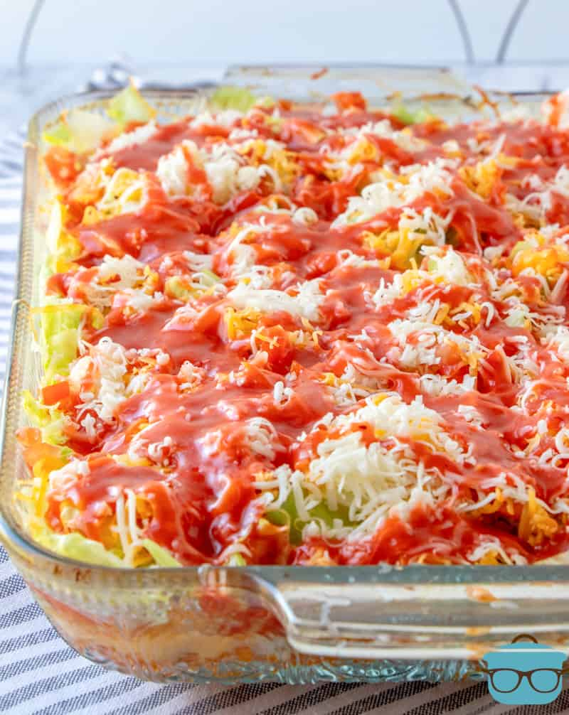 fully assembled Dorito Casserole in a clear baking dish with Catalina dressing drizzled on top
