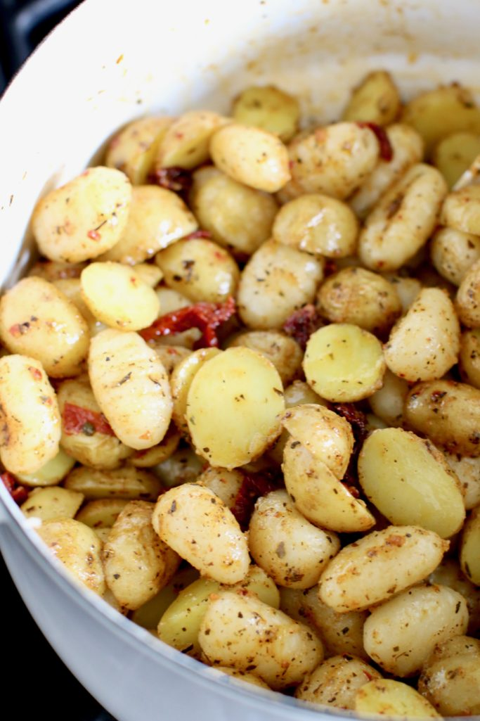 seasoning mixed with potatoes and gnocchi in pot