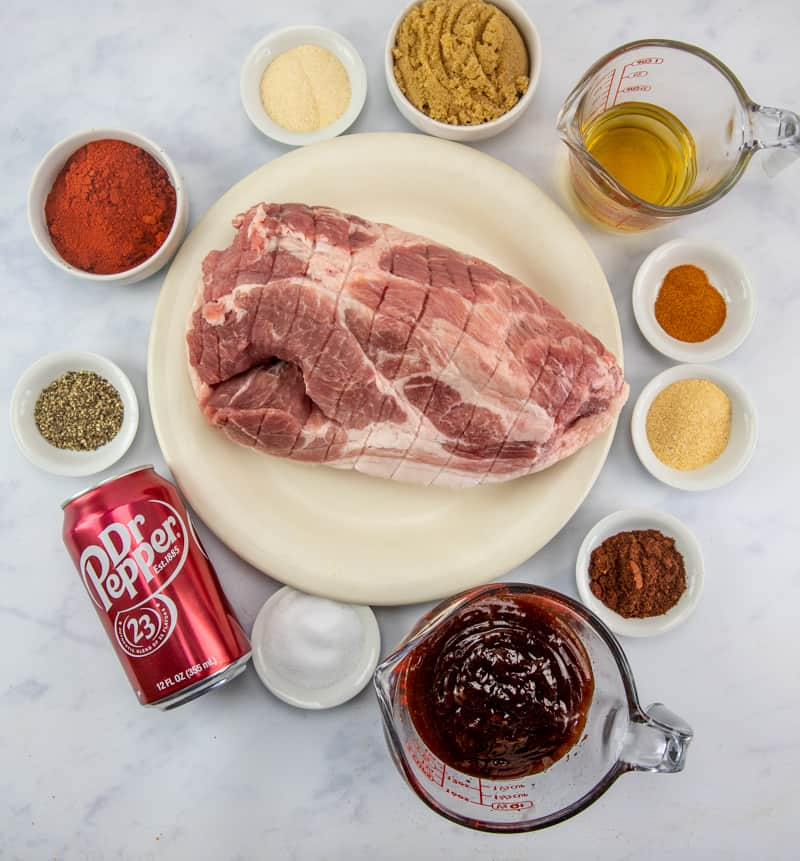 Ingredients for Instant Pot Pulled Pork BBQ: seasoning rub, boneless pork butt, soda (root beer, Dr. Pepper, Coca-Cola), apple cider vinegar, BBQ sauce