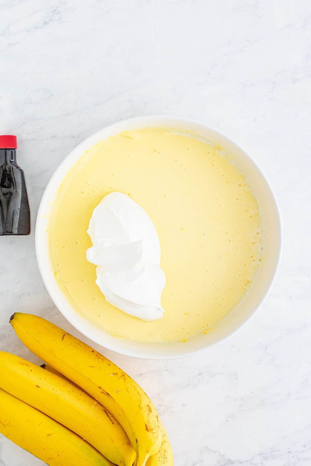 whipped topping added to pudding mixture in a white bowl.