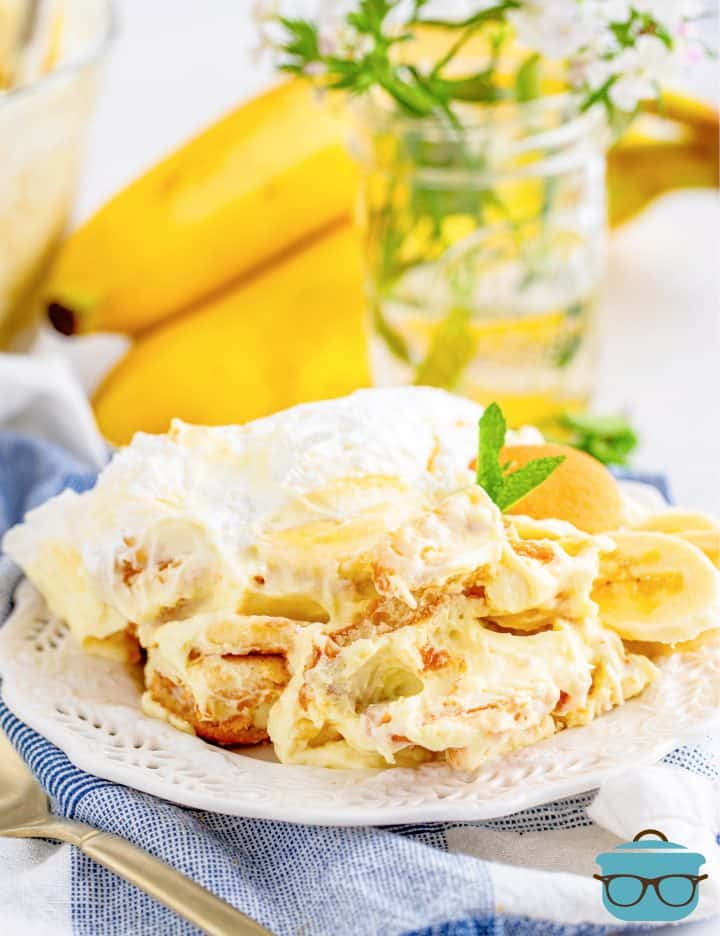 a serving of banana cream pudding on a white plate with a bunch of fresh bananas in the background